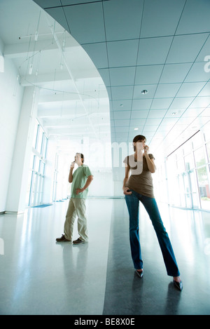 Woman and man standing in lobby, both using cell phones - Stock Photo