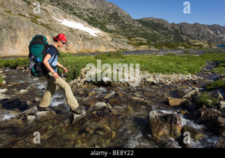 Young woman crossing creek, hiking, backpacking, hiker with backpack, historic Chilkoot Trail, Chilkoot Pass, near - Stock Photo