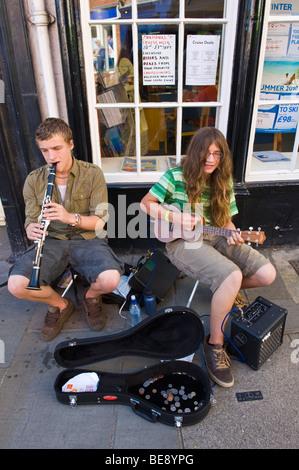 Two teenagers busking playing clarinet and ukulele on pavement during Ludlow Food Festival Shropshire England UK - Stock Photo