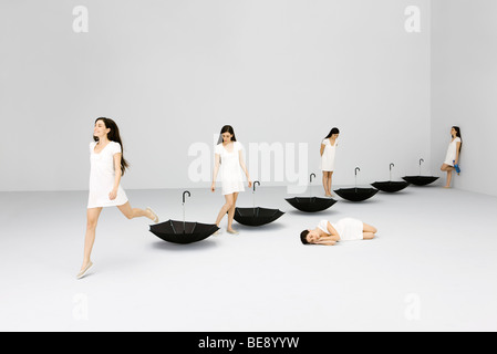 Woman dreaming about self looking at upside down umbrellas, digital composite - Stock Photo