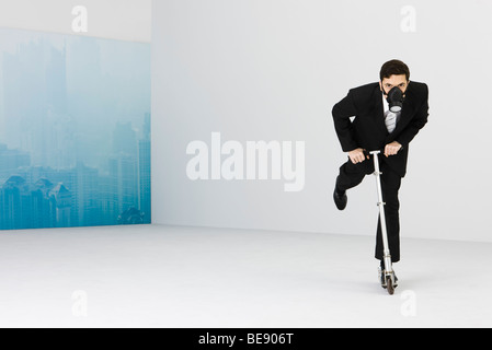 Businessman wearing gas mask riding push scooter, cityscape obscured by smog in background - Stock Photo