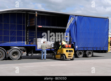 A forklift truck loads unloads a double deck curtainsided trailer and truck