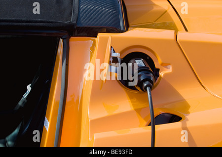 Electric car plugged into a socket, emission-free refueling, charging - Stock Photo