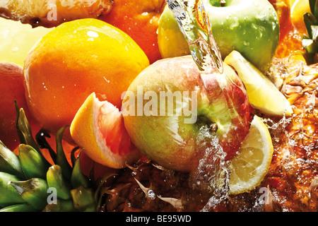 Fruits under water jet, oranges, lemons, grapefruit, apple, pineapple - Stock Photo