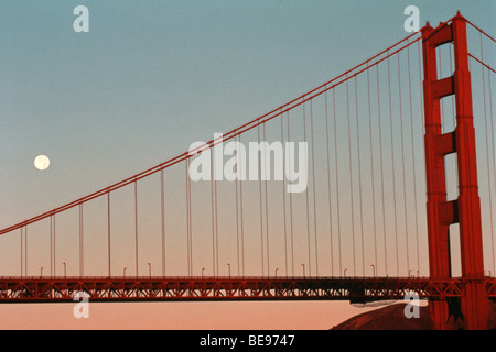 Moon set behind Golden Gate Bridge in San Francisco Bay, California, USA - Stock Photo