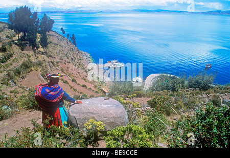 native woman looking across Lake Titicaca from Isla Taquile, Peru - Stock Photo