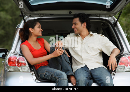 Young couple sitting in car boot - Stock Photo