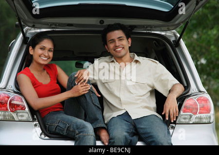 Young couple sitting in car boot smiling at camera - Stock Photo