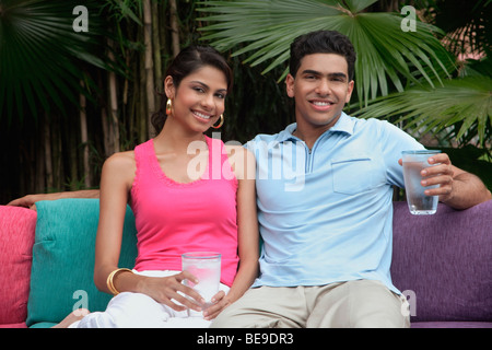 Couple sitting on sofa outdoors, smiling at camera - Stock Photo