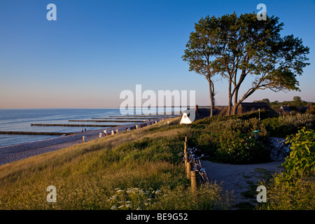View over the coast of Baltic sea in Ahrenshoop, Germany, with a tradtional house and groynes in the evening - Stock Photo