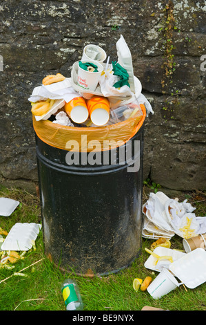 Overflowing litter bin at public park in UK - Stock Photo