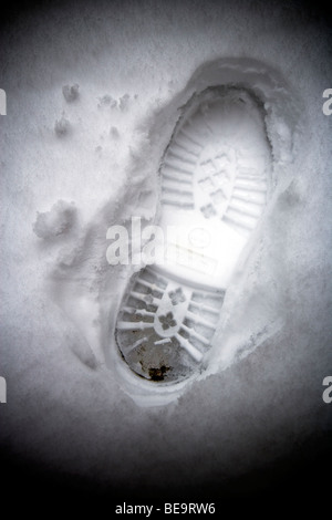 conceptual image of bootprint in snow - Stock Photo