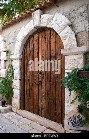 Croatia; Hrvartska; Kroatien, Hvar Island; Strai Grad, aged wooden door, with rounded top, in stone wall - Stock Photo