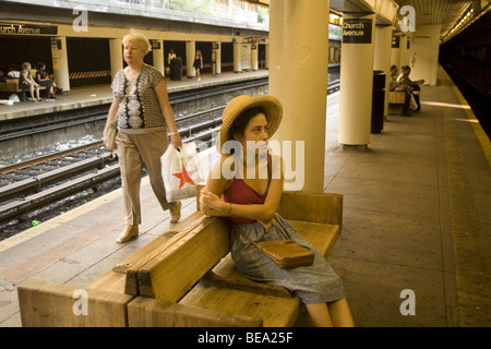 Young woman waits for a Q train at the Church Avenue subway stop in Brooklyn, New York - Stock Photo