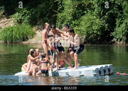 Teenagers playing on a pontoon in the river Lot, Castelmoron, Aquitaine, France - Stock Photo