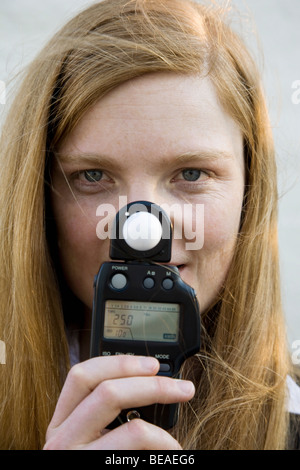 A woman holding a light meter in front of her face - Stock Photo