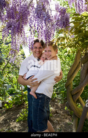 Formal portrait of a mid adult couple and their baby girl - Stock Photo