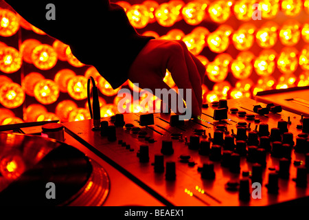 A DJ adjusting levels on a sound mixer at a nightclub - Stock Photo