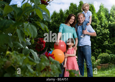 Portrait of a mid adult couple and their two small children - Stock Photo