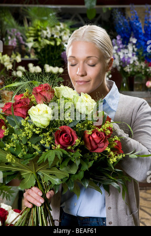 A woman smelling a bouquet of flowers in a florists - Stock Photo