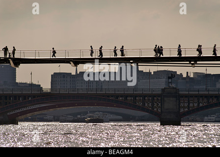 Silhouetted commuters on the Millennium bridge crossing the river Thames. London, England - Stock Photo