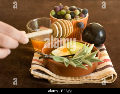 Honey dripping on a green apple slices and other fruits - Stock Photo