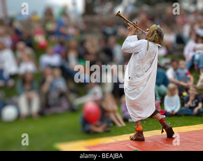 Clown playing a trumpet to an audience outdoors at Abergavenny Food Festival Wales UK - Stock Photo
