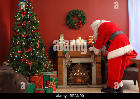 Santa Claus putting Christmas gifts in stockings - Stock Photo