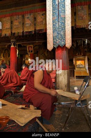 Buddhist monk repairing old Tibetan manuscript, Kumbum Pelkor Chöde monastery, Gyantse, Tibet - Stock Photo