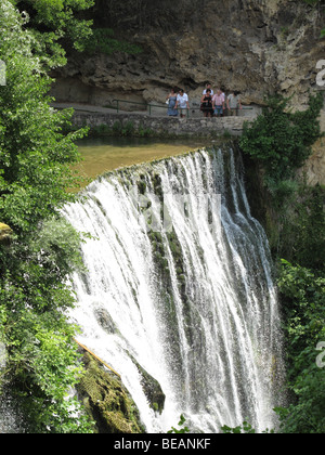Tourist on sightseeing Pliva waterfalls in town of Jajce, Bosnia and Herzegovina - Stock Photo
