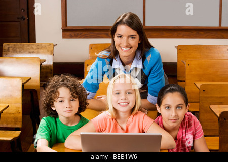Students with their teacher using a laptop in a classroom - Stock Photo