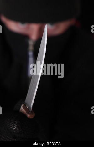 Crime robber criminal mugger with sharp knife about to attack Posed By Model - Stock Photo