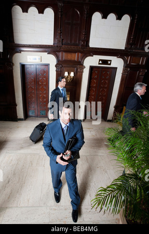 Three businessmen walking in a hotel lobby, Biltmore Hotel, Coral Gables, Florida, USA - Stock Photo