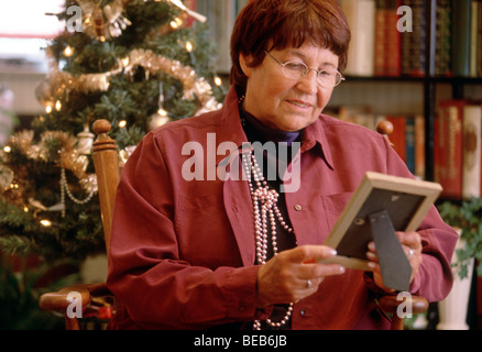 Widow looking at photo frame in front of Christmas tree, she might be missing deceased people or family members - Stock Photo
