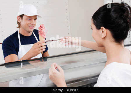 Sales clerk giving ice cream to a customer in an ice cream parlor - Stock Photo
