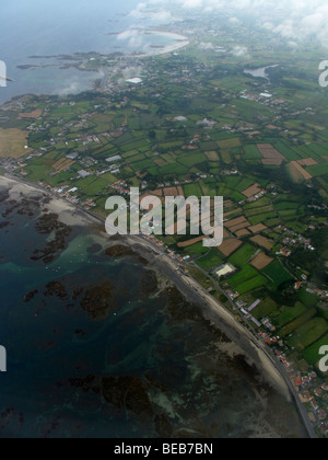 The Guernsey coast is seen from the window of a Flybe airplane during take off on the flight back to Gatwick airport - Stock Photo