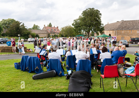 A brass band playing at a fete on the village green on August Bank Holiday in the Cotswold village of Willersey, - Stock Photo