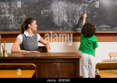Schoolboy pointing at a blackboard with a teacher in a classroom - Stock Photo