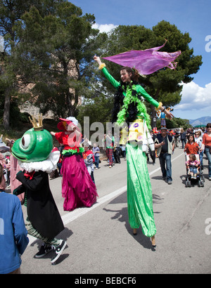 Festival with female stiltwalker and people in costume Fiesta of the Angel Bellver Castle Palma Mallorca Spain - Stock Photo