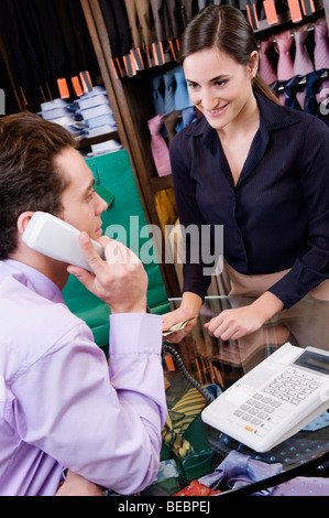 Salesman talking on the telephone in a clothing store - Stock Photo