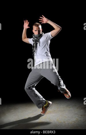 Portrait of hip hop young man dancing over dark background - Stock Photo