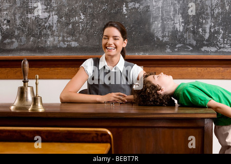 Schoolboy bending backward on a table with his teacher smiling - Stock Photo
