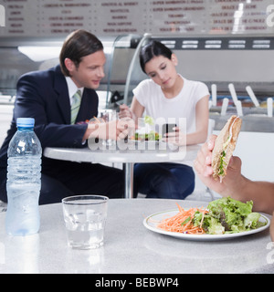 Couple text messaging on a mobile phone in a restaurant - Stock Photo