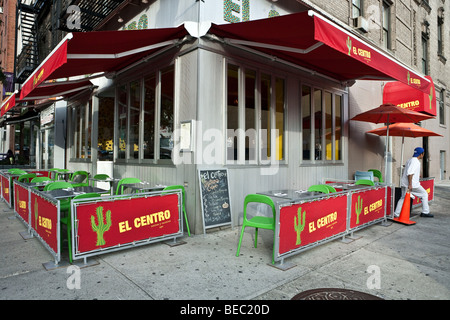 corner Mexican restaurant with awning & sidewalk seating in Mexican colors in New York City Hells Kitchen neighborhood - Stock Photo