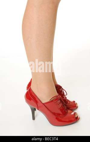 Woman standing wearing a pair of red lace up high heeled shoes - Stock Photo