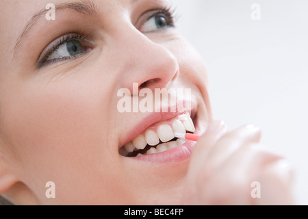 Woman cleaning teeth with interdental brush. - Stock Photo