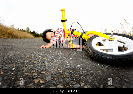 Child boy  cycling bicycle on the country road with bike helmet, falling down, accident - Stock Photo
