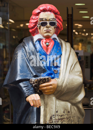 Beethoven statue with red hair, sunglasses and colourful clothing in front of a retail outlet - Stock Photo