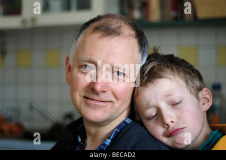 Little boy, 8, leaning against his father's shoulder - Stock Photo