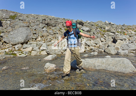 Young woman, hiker with backpack, hiking, crossing creek, balancing on rocks, historic Chilkoot Pass, Chilkoot Trail, - Stock Photo